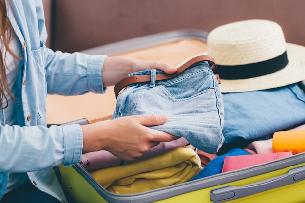 Woman traveler pack a suitcase at home for a new journey. vacation travel luggage for holidays and adventures