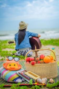 Женщина-путешественник играет на гитаре и пикник на пляже.