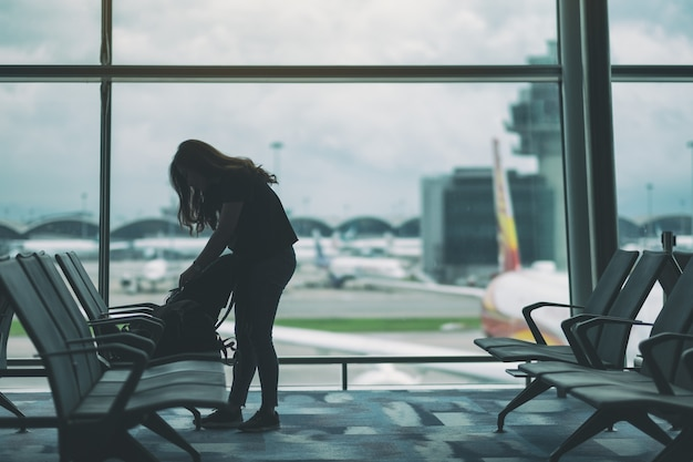 A woman traveler preparing and packing her bag in the airport