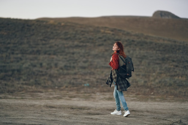 Woman traveler in a red jeans sweater with a backpack on her back in the mountains