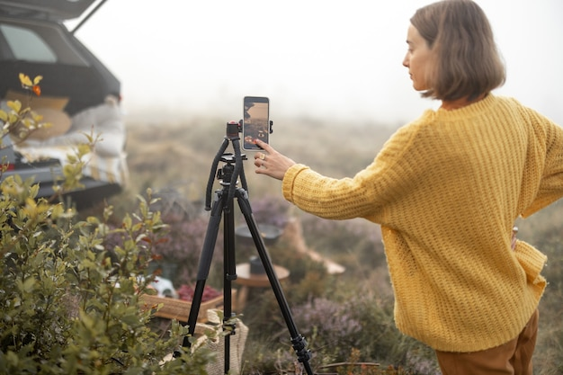 Woman traveler shooting on phone her picnic while travel