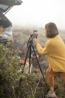 Woman traveler shooting some video on phone, at picnic while traveling in the mountains
