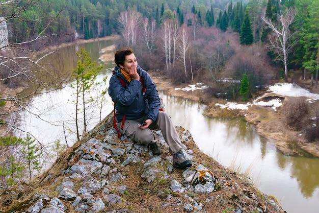 女性旅行者は森の中の春の川の上の崖に座って遠くに叫びます