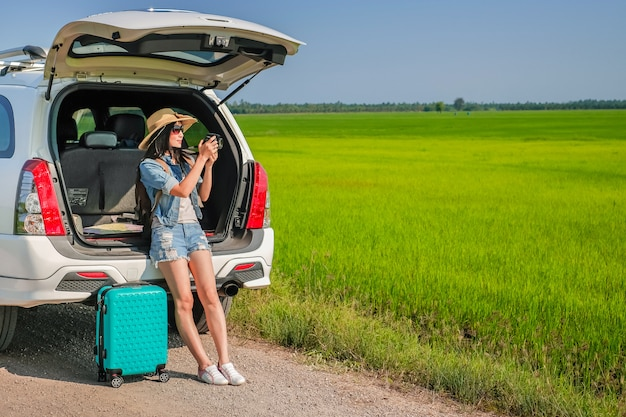 Woman traveler sitting on hatchback of car and taking photo