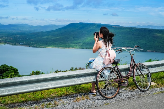 Woman traveler sitting near a bicycle and taking photo view of dam