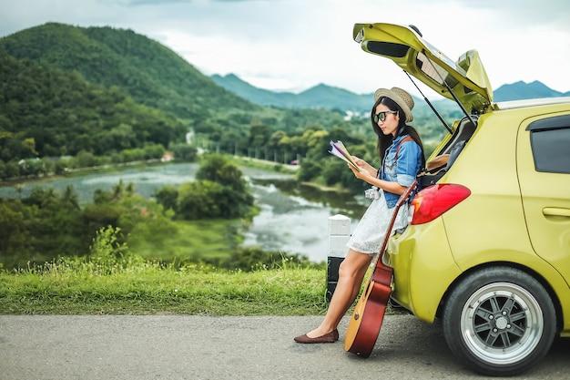 Женщина-путешественник, сидя на хэтчбек автомобиля и глядя на карту, чтобы найти путь на vaca