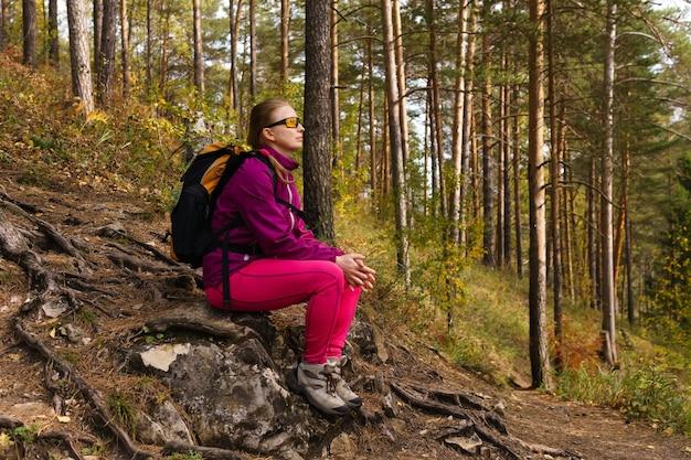 Женщина-путешественница сидит на камне на склоне горы среди осеннего леса