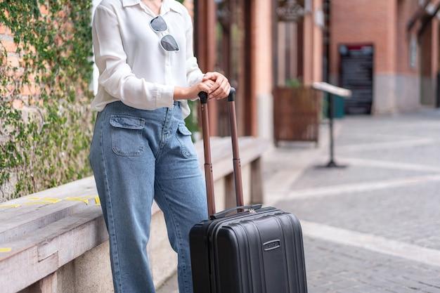 空港で搭乗する乗客に歩いてスーツケースの荷物を立ってドラッグする女性旅行者
