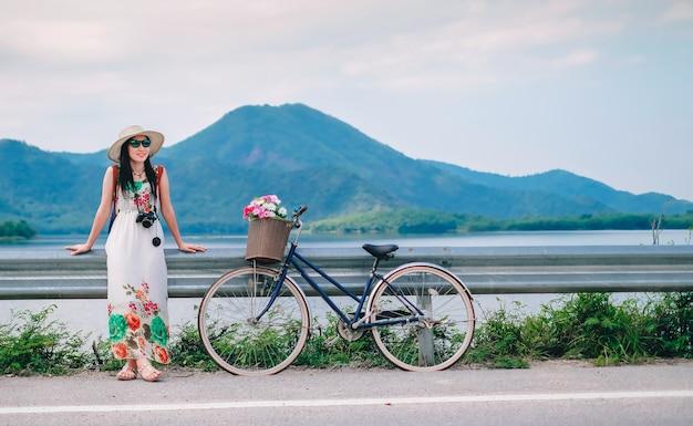 Женщина-путешественник, стоящая рядом с велосипедом и счастливая для вида на природу у озера на вакууме