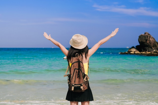 Woman traveler standing and happy on the beach.