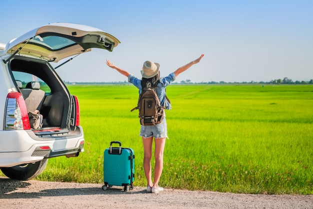Woman traveler standing near hatchback of car during go to travel on  holiday