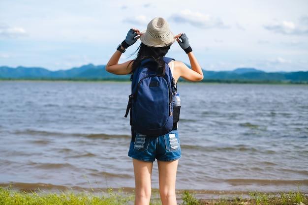 Женщина путешественник стоит возле озера фон гора
