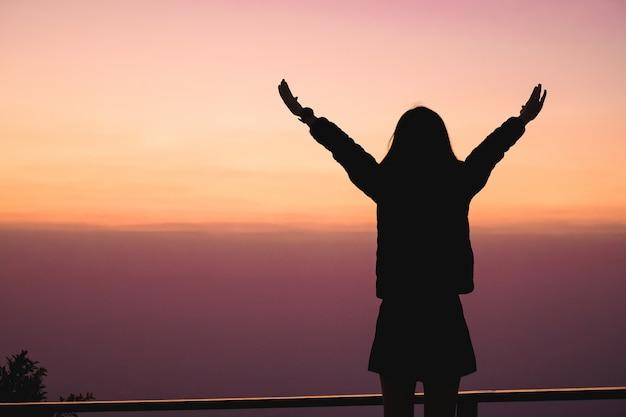 Путешественник женщины стоя на верхней части горы и наслаждаясь для взгляда природы когда заход солнца.