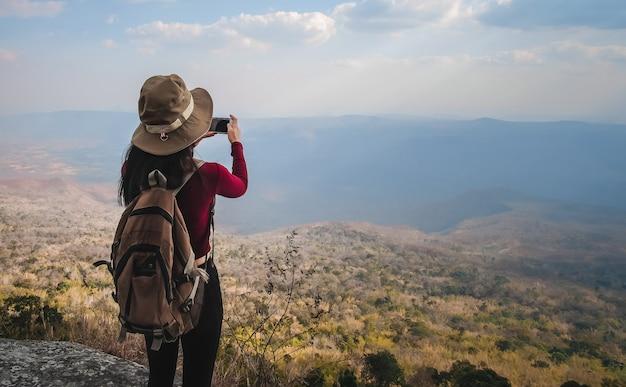 Путешественник женщина, стоя на вершине горы и принимая фото вид природы на праздник.