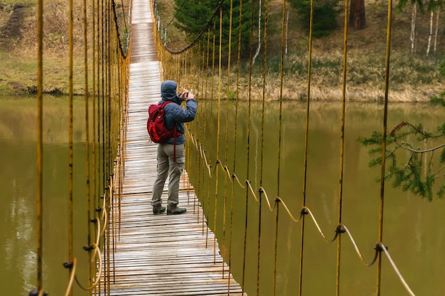 女性旅行者が春の川に架かる吊橋に立って写真を撮る