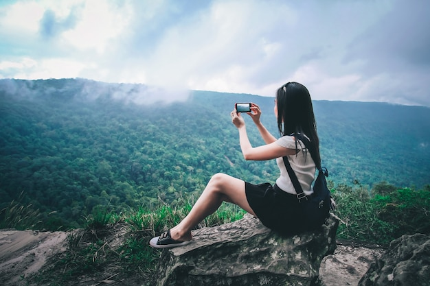 Woman traveler taking photo view of nature on top of the mountain during vacation.