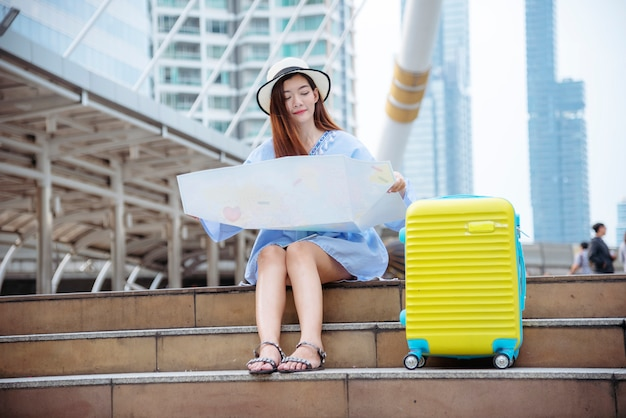 Woman traveler tourism with travel suitcase on vacation summer dream asian destination holding map for tourist looking on journey
