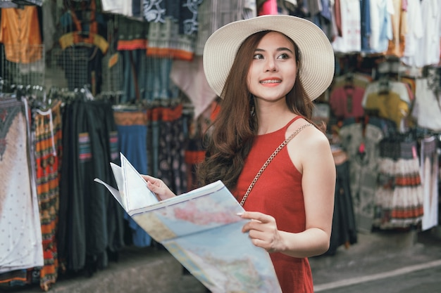 Woman traveler tourist with map traveling on walking street. journey trip travel