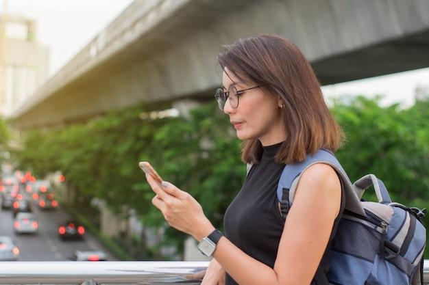 女性旅行者はスマートフォンを使用して、バンコクの旅行マップを検索します。