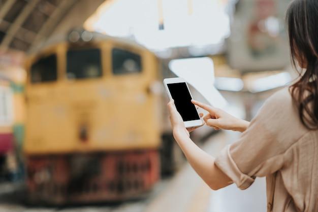 Женщина-путешественник, используя пустой экран мобильного телефона на вокзале