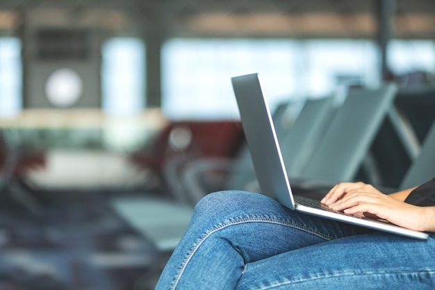 A woman traveler using laptop computer while sitting in the airport