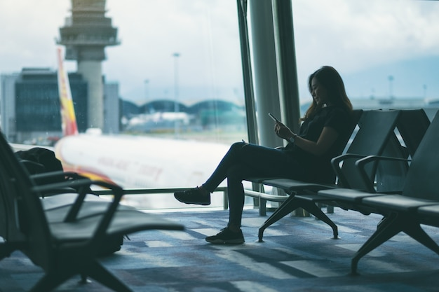A woman traveler using mobile phone while sitting in the airport