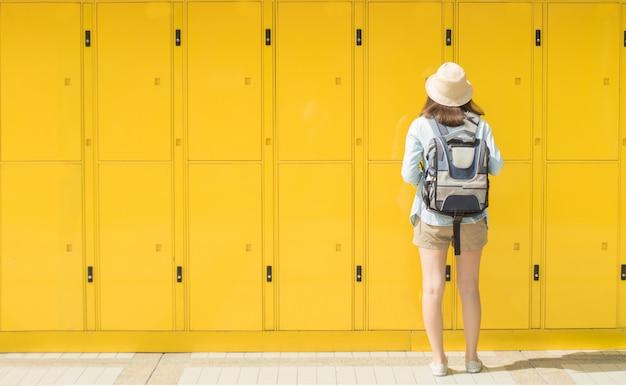 Женщина-путешественница пользуется шкафчиком сервиса и отправляется на отдых в город