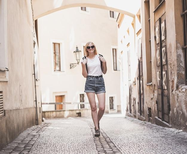 Путешественник женщина, идущая через аркаду в европейском историческом городе. хипстерская девушка, путешествующая по европе. концепция туризма