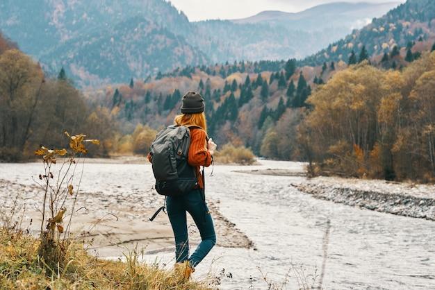 女性旅行者は、川の風景モデルの帽子の赤い髪の近くの山で自然の中を歩きます