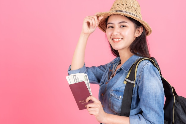Woman traveler wearing straw hat is holding passport with banknote