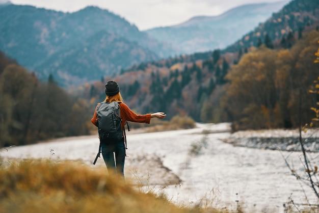 가을 산에서 강 근처에 배낭과 모자에 여자 여행자