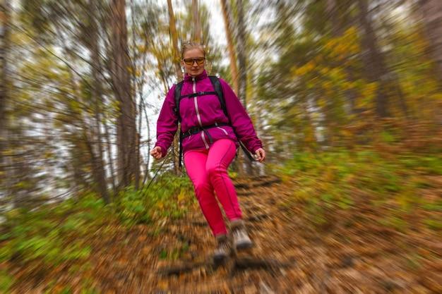 Женщина-путешественница с рюкзаком спускается с холма по тропе в осеннем лесу, радиальное размытие фона