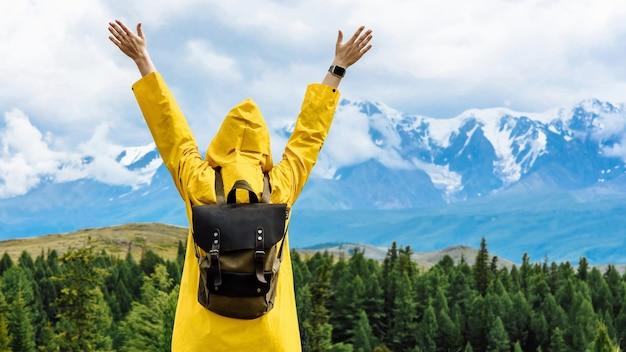 バックパックを持った女性旅行者は、手を上げて山を見ます。旅行とアクティブライフのコンセプト。山での冒険と旅行