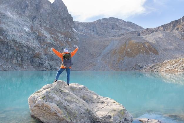 湖の上の崖の山で重いバックパックを持った女性旅行者旅行ライフスタイルアドベンチャー