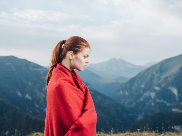 山の肩に赤い格子縞の女性旅行者。