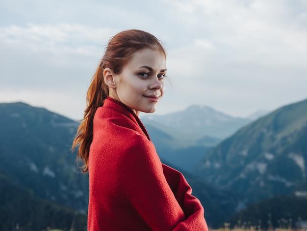 산에서 그녀의 어깨에 붉은 격자 무늬와 여자 여행자