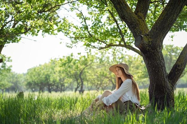 素晴らしい森に座っているバックパックと帽子、放浪癖の旅行のコンセプト、テキストのためのスペース、雰囲気のある瞬間を持つ女性旅行者。アースデー
