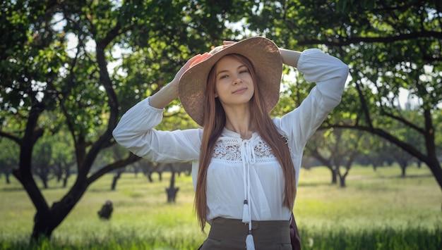 素晴らしい森の中を歩くバックパックと帽子、放浪癖の旅行のコンセプト、テキストのためのスペース、雰囲気のある瞬間を持つ女性旅行者。アースデー