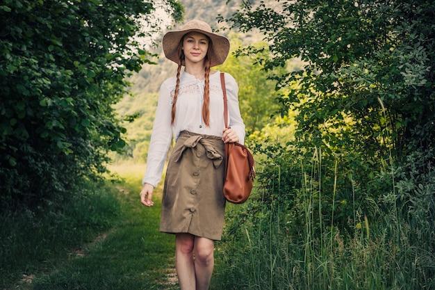 배낭과 놀라운 산과 숲, 방랑 여행 개념, 텍스트를위한 공간, 대기 순간에서 걷는 모자를 가진 여자 여행자. 지구의 날