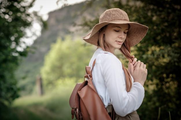 素晴らしい山と森を歩くバックパックと帽子をかぶった女性旅行者、放浪癖の旅行のコンセプト、テキストのためのスペース、雰囲気のある瞬間。アースデー
