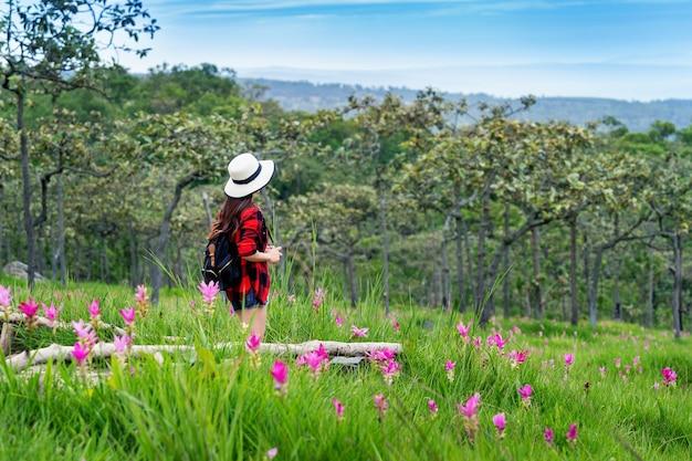 タイのクラシューフラワーフィールドでバックパックを楽しんでいる女性旅行者。旅行のコンセプト。