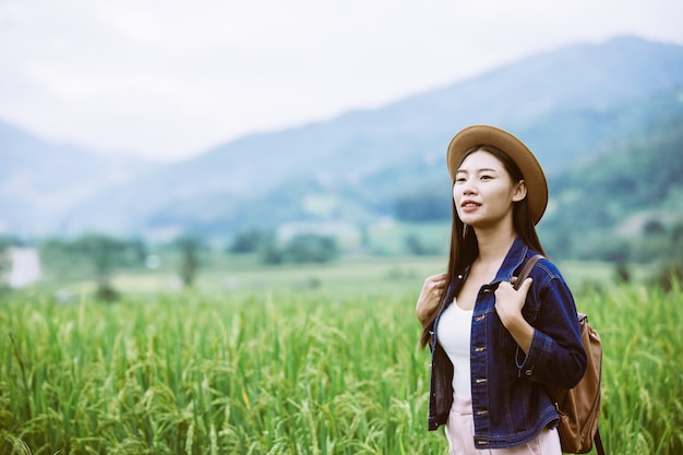 Woman traveler with backpack  hat and looking at lies on a meadow in the mountains.