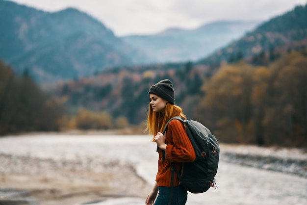 Woman traveler with a backpack and in a hat near the river in the mountains in autumn