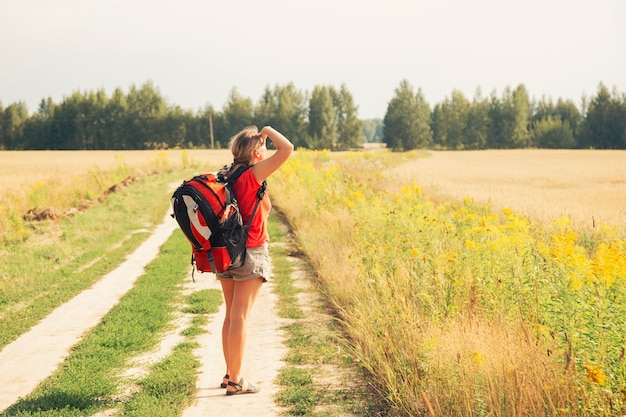 Женщина-путешественница с рюкзаком, походы в горы с красивым летним пейзажем