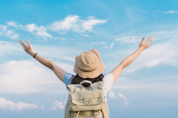 Путешественник женщины при рюкзак держа шляпу и смотря голубое небо, концепцию перемещения, космос для текста и атмосферный момент