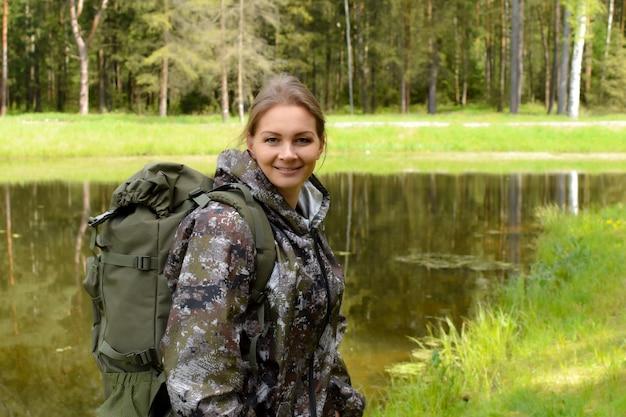 夏の森のバックパックを持つ女性旅行者