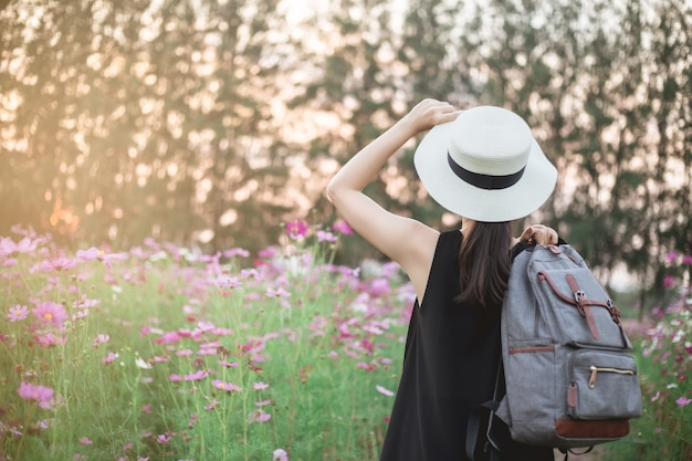 Woman traveler with backpack and looking at amazing beautiful flower fields