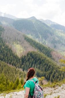 놀라운 산과 숲, 방황 여행 개념, 텍스트를위한 공간을보고 배낭을 가진 여자 여행자