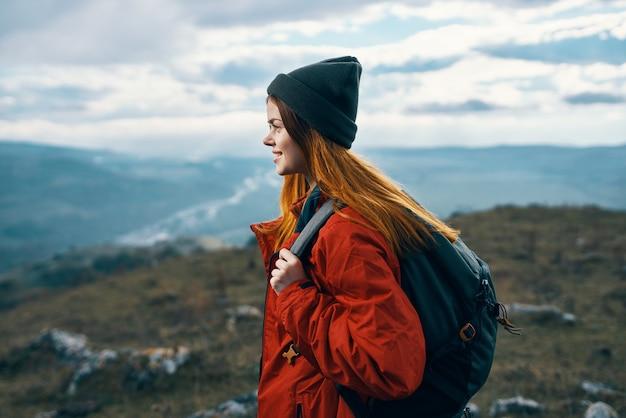 バックパックの山の風景の自由を持つ女性旅行者