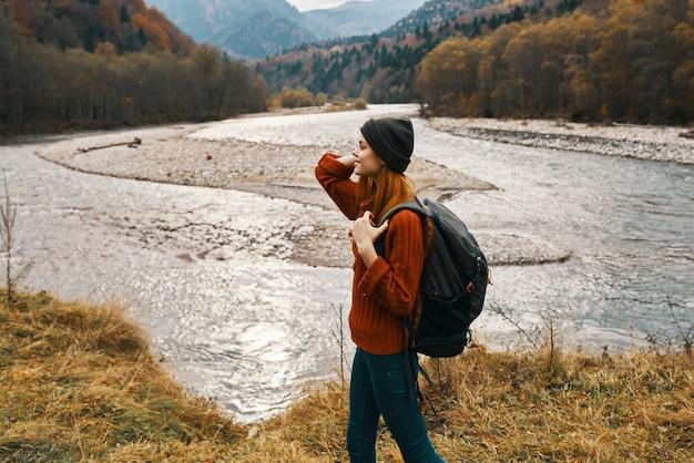 山の側面図の川岸にバックパックを持つ女性旅行者